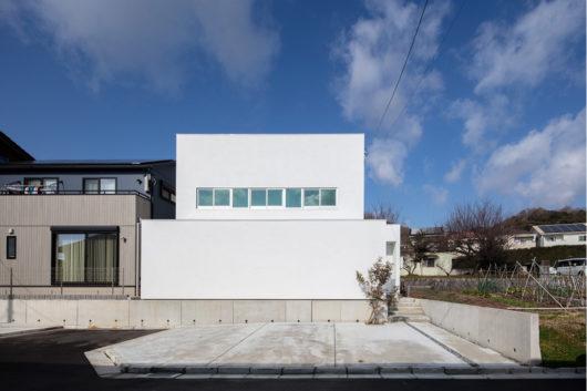 白いシンプルな外観とゆったりとした駐車場スペース