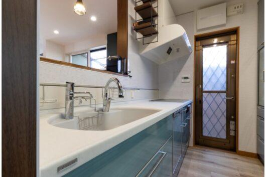 人造大理石の美しさが映えるキッチン。レンジフードの横のスペースも飾り棚にして。